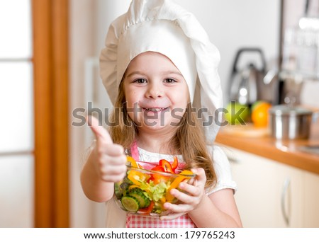 Kid girl with healthy food and showing thumb up