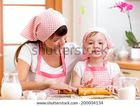 kid girl with her mother cook and roll out the dough - stock photo