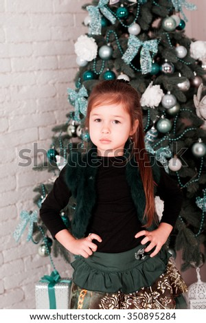 Kid girl 4-5 year old standing over Christmas tree in room. Looking at camera. Merry Christmas. Happy New Year. Celebration holidays.  - stock photo