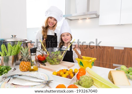 Kid girls junior chef friends hug together in countertop with food at cooking school - stock photo