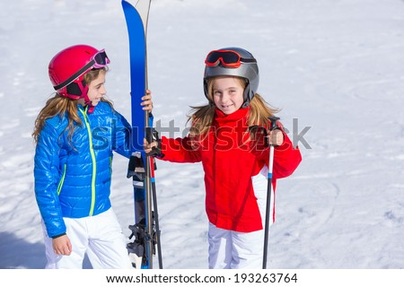 Kid girls sister in winter snow with ski equipment helmet goggles poles - stock photo