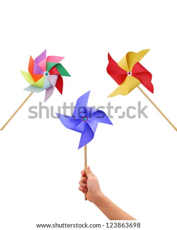Kid hand holding a blue pinwheel close up and colorful pinwheel on white background. - stock photo