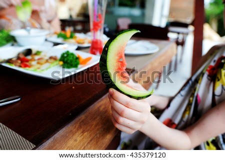 Kid hand holding piece of carved watermelonin the restaurant