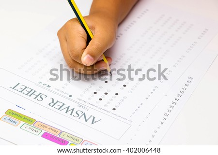 kid hand marking on answer sheet for question word