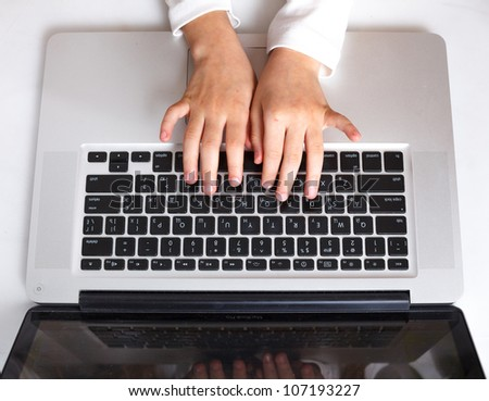 Kid hand on keypad of laptop at workplace