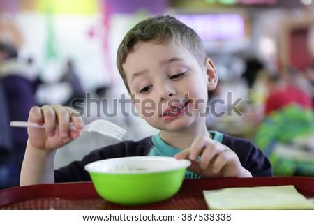 Kid has meat dumplings in the fast food area - stock photo