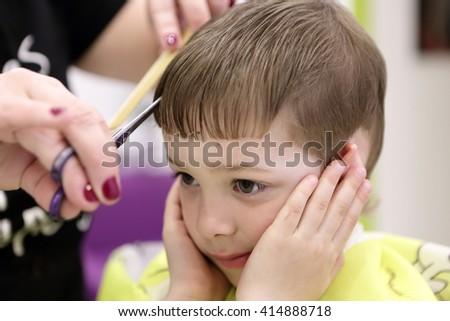 Kid having a haircut at the barbershop - stock photo