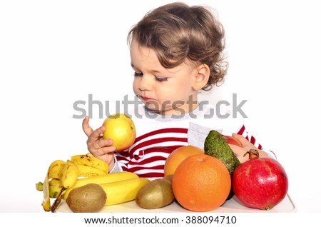 Kid having a table full of organic food. Cheerful toddler eating healthy salad and fruits. Baby choosing between apples, bananas, oranges, avocado,pomegranate. kiwi. Isolated on white
