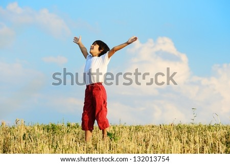 Kid having happy carefree time on yellow wheat field - stock photo