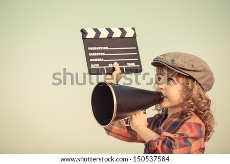 Kid holding clapper board and shouting through vintage megaphone. Cinema concept. Retro style - stock photo