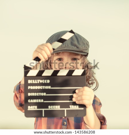 Kid holding clapper board in hands. Cinema concept. Retro style - stock photo