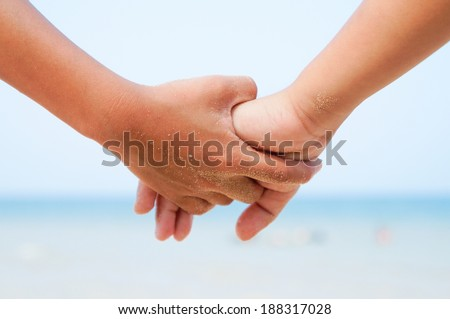 Kid holding hands on the in blur beach background.