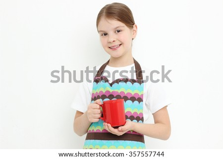 Kid holding red mug (tea cup) - stock photo