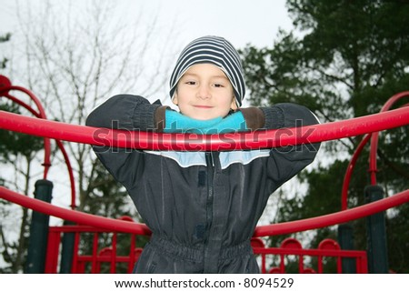 Kid in a playground a cold autumn day