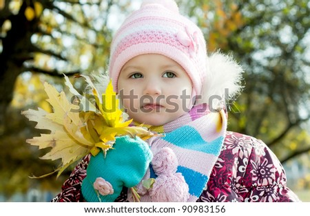 Kid in autumn with leaves of maple