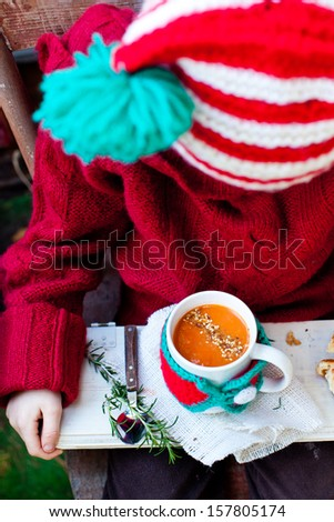 Kid in Christmas Hat holding a Mug of Tomato Soup with Seeds. Also available in horizontal format.  - stock photo