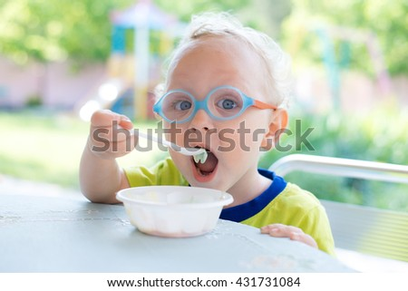 Kid in glasses eating at the table outdoors