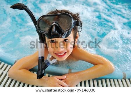 Kid in pool with diving equipment - stock photo