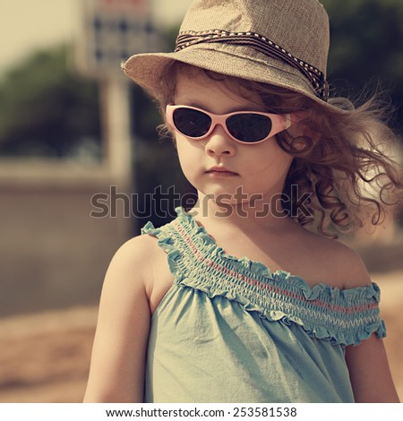 Kid in sun glasses and fashion hat outdoors. Vintage closeup portrait - stock photo