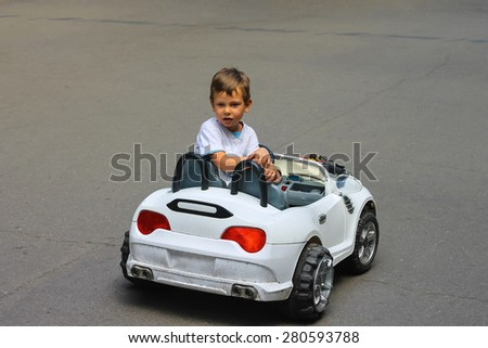 Kid in the park riding a toy car - stock photo