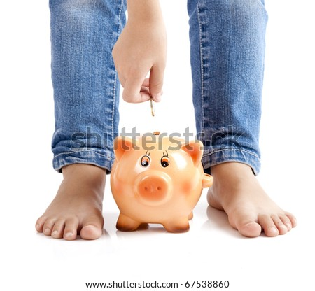 Kid inserting one euro coin on the piggy-bank - stock photo