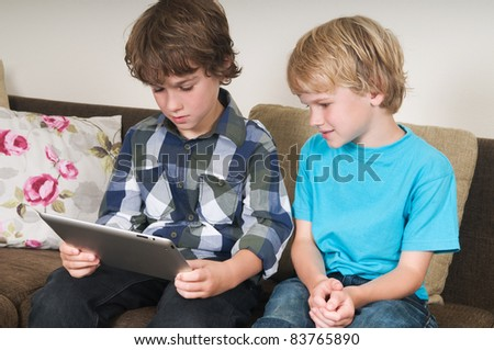 Kid is working on a tablet computer while his brother is watching