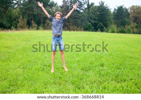 Kid jumping on the meadow in a summer forest - stock photo