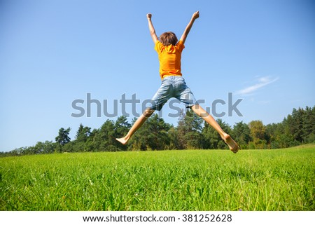 Kid jumping on the sunny meadow in a summer - stock photo