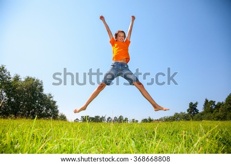 Kid jumping on the sunny meadow in a summer forest - stock photo