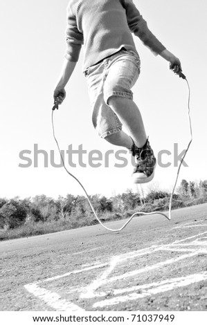 kid jumping rope on playground - stock photo