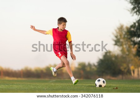 kid kicking a soccer ball on the field - stock photo