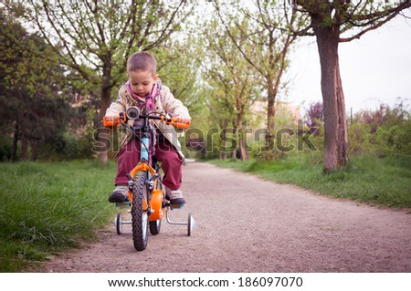 kid learning to ride the  bicycle in the park
