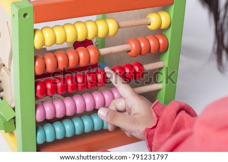 Kid learns on mathematic concept using colorful counting beads or abacus.
