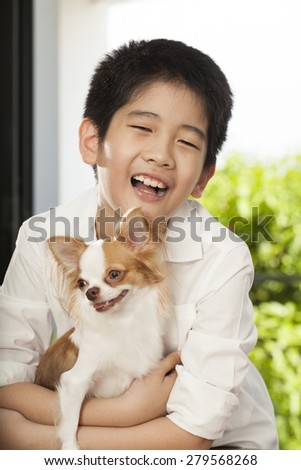 kid life, an Asian boy hug his friend Chi hua hua tiny dog - stock photo