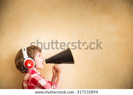 Kid listen music at home. Hipster child with retro vintage speaker - stock photo