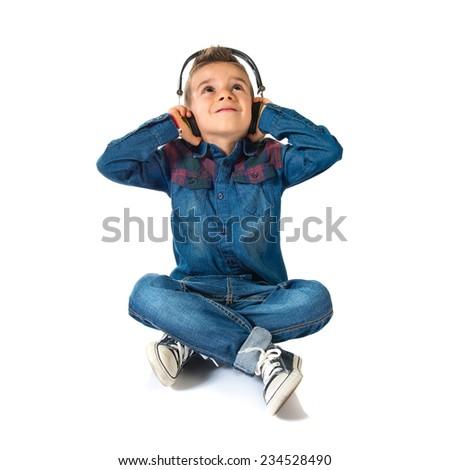 Kid listening music over white background - stock photo