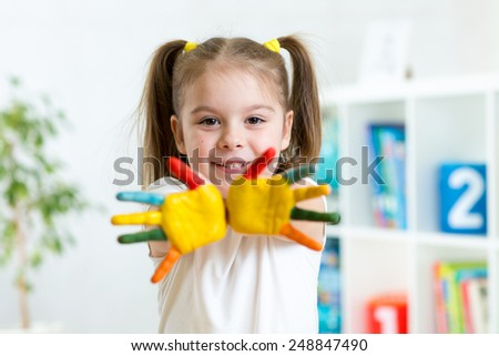 kid little girl with hands in paint on nursery background - stock photo