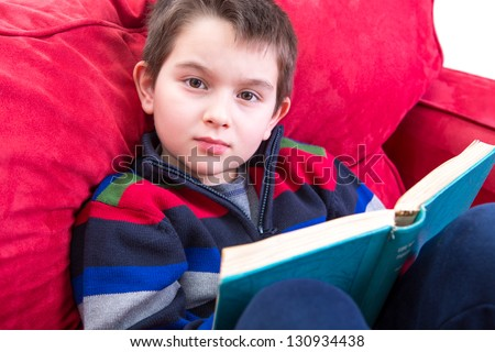 Kid looking at camera while reading a book on the red couch. He has a meaningful look on his face, perhaps distracted. - stock photo
