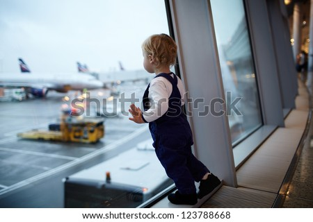 Kid near the window in the airport. - stock photo
