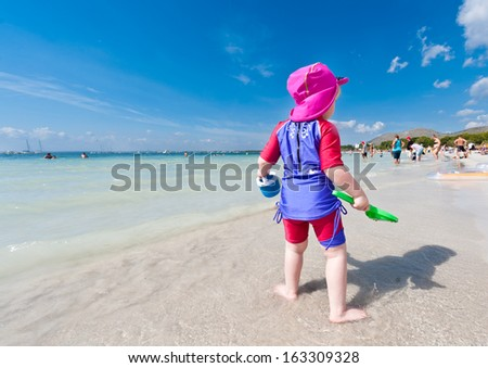 Kid on beach looking away from camera - stock photo