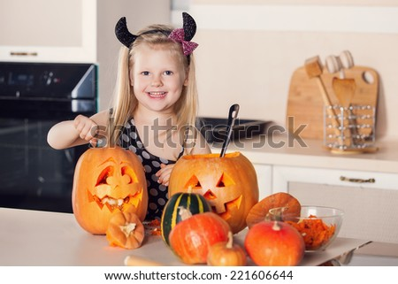 Kid on Halloween party making carved pumpkin - stock photo