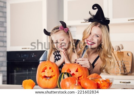 Kid on Halloween party making carved pumpkin with a little help from her mother