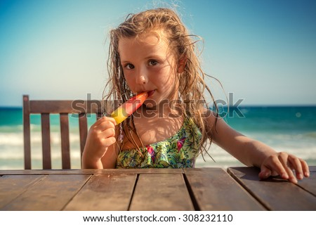 kid on table eating icecream - stock photo