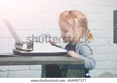 kid or small boy or businessman child sitting at table and typing typewriter with paper on white brick wall background, business and new technology