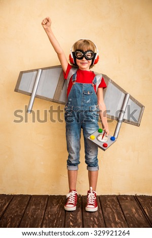 Kid pilot playing with toy jet pack at home. Success and leader concept - stock photo
