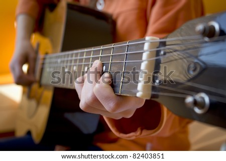 Kid playing a guitar, focus on the hand holding the fretboard - stock photo
