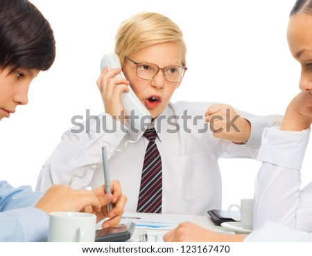 Kid playing angry businessman adult rearing to telephone as he sits on a meeting with his employees - stock photo