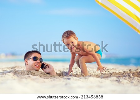 kid playing around father's head in sand, talking on the cell phone - stock photo