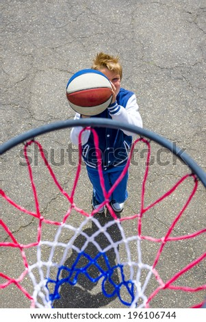 kid playing basketball photographed from above the ring - stock photo