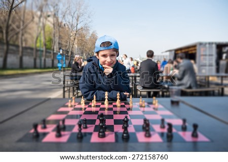 Kid playing chess along Seine river. Paris, France. - stock photo
